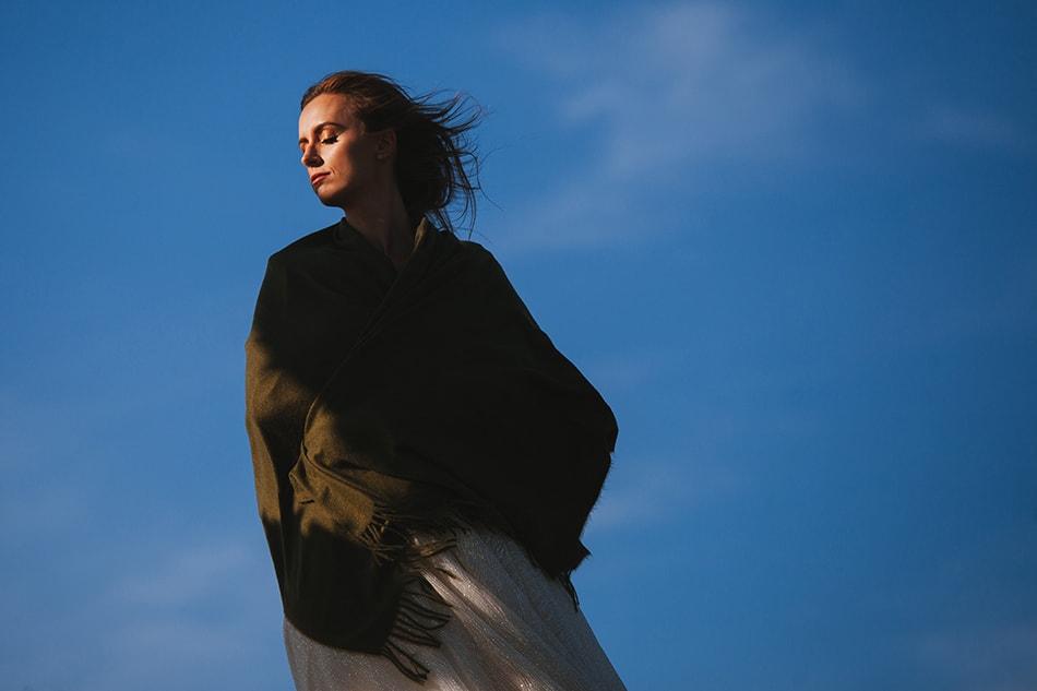 pani młoda stoi zwrócona twarzą do słońca, jej włosy rozwiewa wiatr