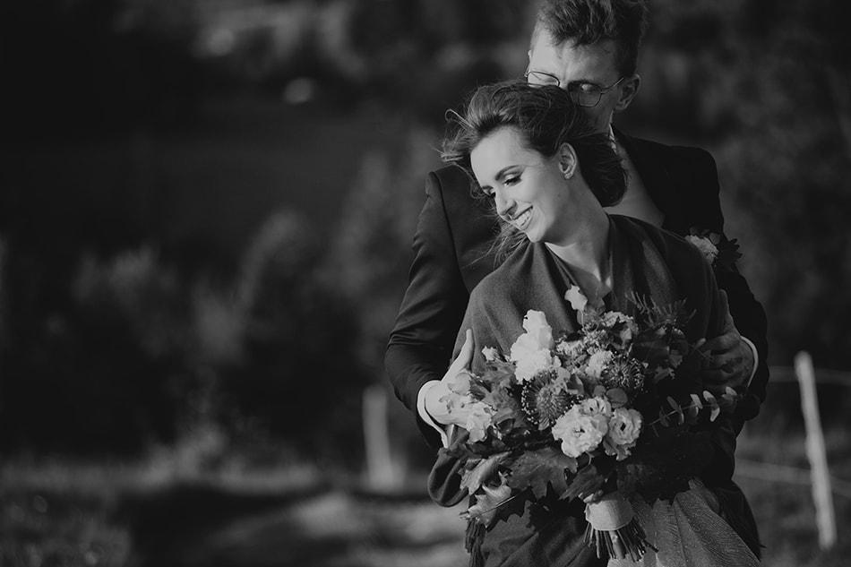 mężczyzna przytula się do kobiety, ona uśmiecha się wesoło, w rękach trzyma bukiet ślubny