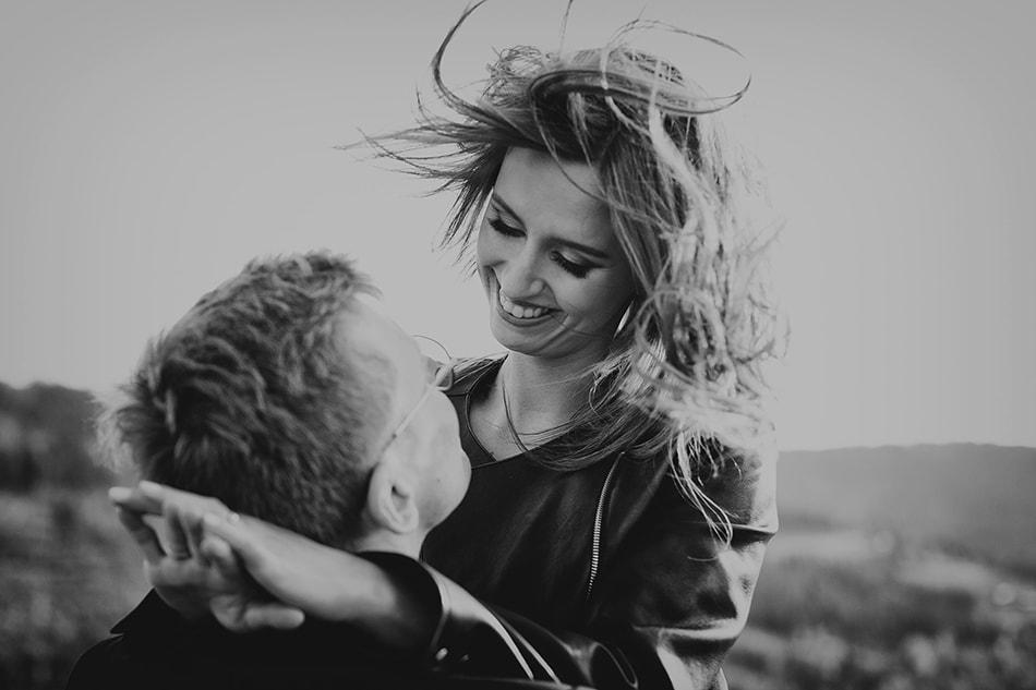 dziewczyna zarzuca ręce na ramiona chłopaka, jej włosy rozwiewa wiatr