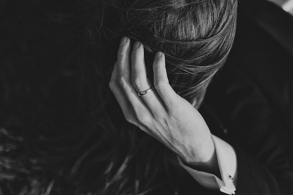ręka mężczyzny dotyka włosów kobiety, obrączka błyszczy w zachodzącym słońcu