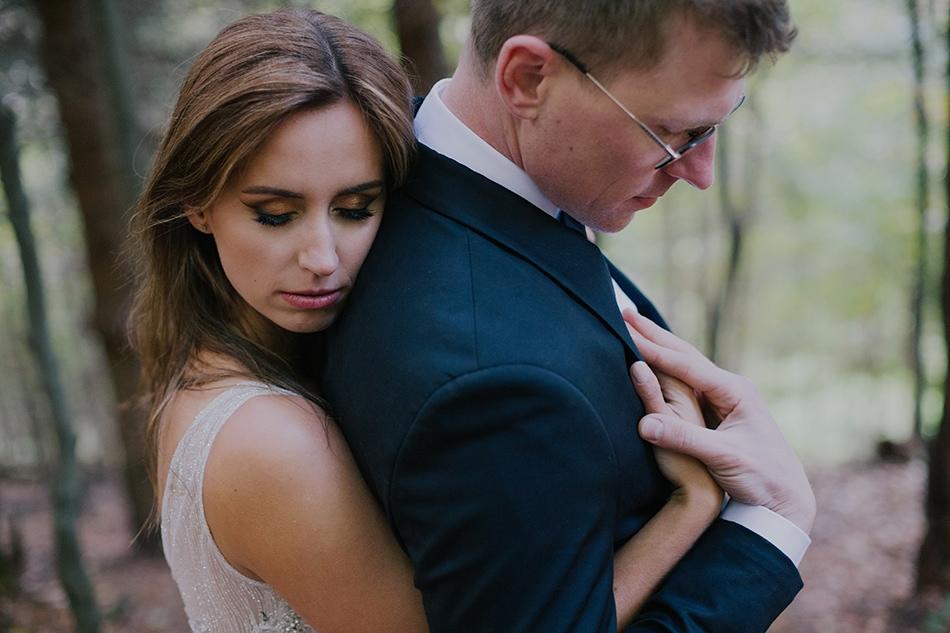 młodzi małżonkowie stoja w lesie, kobieta przytula się do ramion mężczyzny