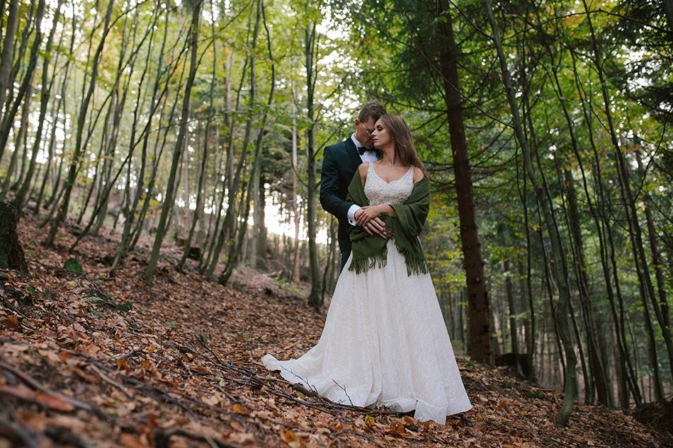 para młoda stoi w jesiennym lesie, mężczyzna przytula się do kobiety