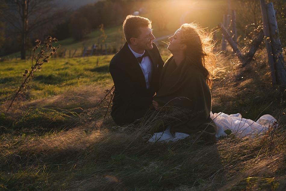 młodzi siedzą na trawie, naprzeciw siebie, sa otuleni kocem, w tle widać promienie zachodzącego słońca